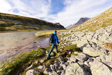 Rondane National Park, Norway: A male hiker hiking along the the river that flows from the Rondvassbu lodge towards Otta and comes by the parking in Spranget.