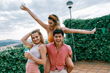a latina, russian and an asiatic man drinking mojitos at a party in a cloudy summer day