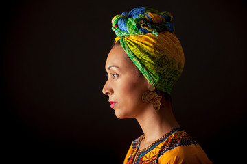 Side view of studio portrait of Young African woman in ethnic clothing, africa shaped earrings and turban on head thoughtfully looking away