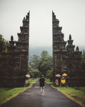 Back view of male traveler running on paved roadway into ancient mossy gates of temple, Bali