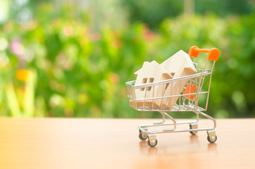 Two wooden houses in a trading cart on nature background. The concept of buying and selling real estate, renting. Attractive investing. rising prices. supply and demand, rates of sales