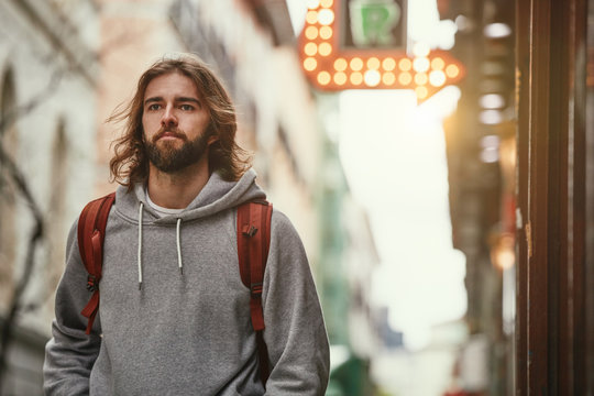 Young bearded handsome man in grey hoodie with backpack seriously walking outside