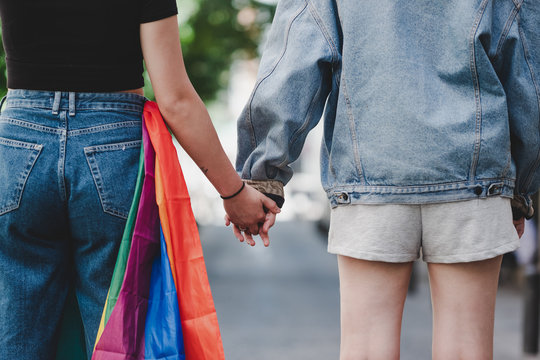 Back view of crop women with LGBT flag holding hands while standing on blurred background of city street