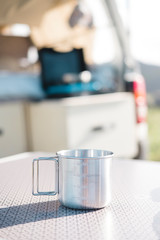 Close up of a camping mug on table with camper van in background