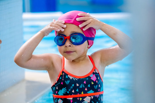 Little ethnic girl in swimwear and goggles touching wet hat and looking away while standing near swimming pool