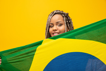 Afro girl cheering for favorite brazilian team, holding national flag in yellow background.
