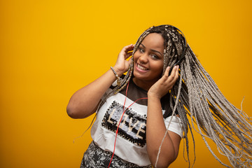 African American girl listening to music on a headphones on yellow background