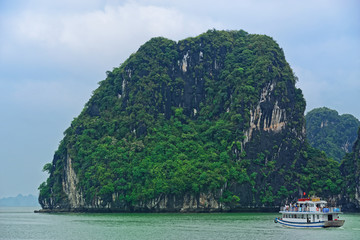Tourist junk floating along limestone rocks at Ha Long Bay, Vietnam