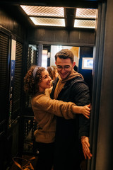 Side view of cheerful young man and woman holding door of elevator and smiling during romantic date