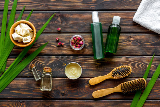 Cosmetics for hair care with jojoba, argan or coconut oil in bottle on wooden background top view