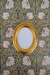 Oval golden picture frame on wallpaper with Art Nouveau floral design