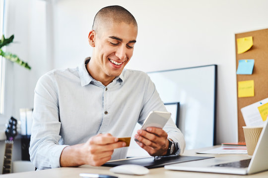 Young man sitting in home office paying online with credit card and smartphone