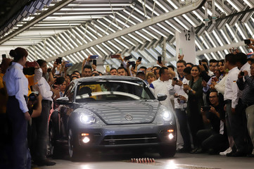 Employees take pictures of a Volkswagen Beetle car during a ceremony marking the end of production of VW Beetle cars, at company's assembly plant in Puebla