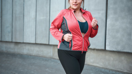 Morning workout. Young plus size woman in sport clothes running outdoors. Healthy lifestyle. Weight losing