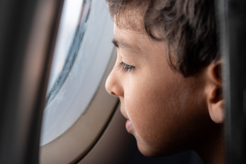 Boy looking out of airplane window