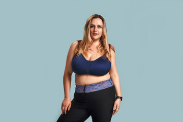 I choose healthy life Confident and beautiful plump woman in sport clothes looking at camera while standing against blue wall