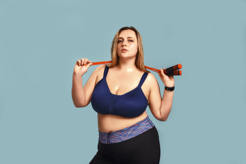 Confident pretty plump woman in sport bra holding a jumping rope at her shoulders and looking at camera while standing against blue wall.