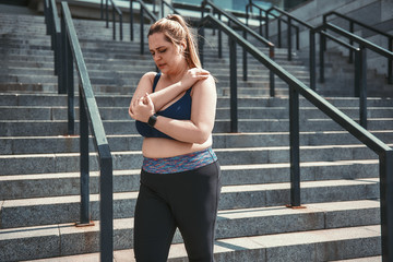 Pain after workout. Tired plus size woman in sport clothes suffering from shoulder pain while standing on stairs.