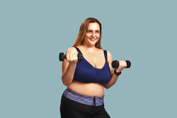 Weight exercise. Beautiful and positive plus size woman in sport clothes holding dumbbells and smiling while standing inside against blue wall.