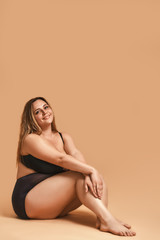 Chubby woman. Vertical photo of plus size sexy model in black lingerie sitting on the floor and smiling while posing in studio