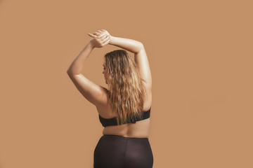 Back view of plump sexy woman with long hair in sexy black lingerie raising hands up and posing in studio on brown background