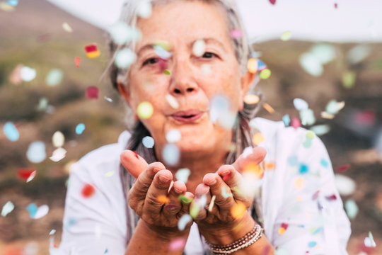 Senior woman blowing confetti outdoors