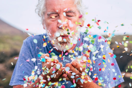 Senior man blowing confetti outdoors