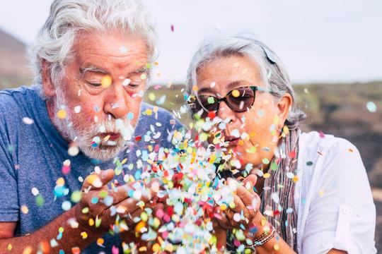 Senior couple blowing confetti outdoors