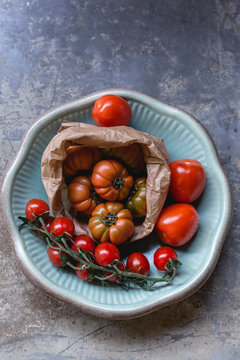 Sardinian beef tomatoes in paper bag, ripe of mini plum tomatoes and Roma tomatoes on plate