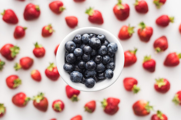 top view of sweet blueberries on bowl and strawberries on background