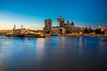UK, London, Skyline at night with Hms Belfast in the foreground