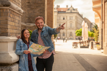 two friends, or couple, looking at a city map while one man is pointing finger. Location Novi Sad, Serbia.