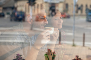 two friends drinking coffee in a cafe. Shot thought window with reflections.
