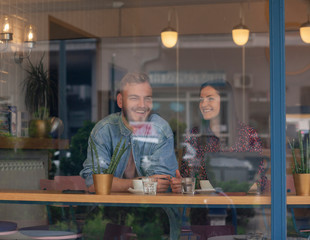 two friends talking in a cafe. Shot through window with street reflections.