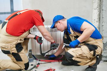 two plumber at work. Installing water heating radiator