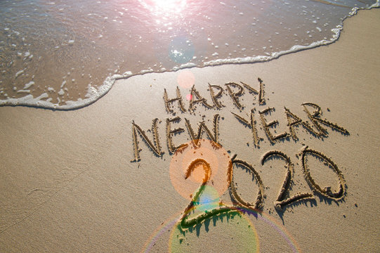 Happy New Year 2020 message handwritten in raised textured letters on a sand beach with smooth copy space next to oncoming wave