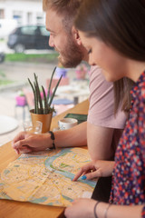 two friends sitting together in cafe, while searching on a city map.