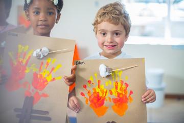 Portrait of smiling children presenting images of fire in kindergarten