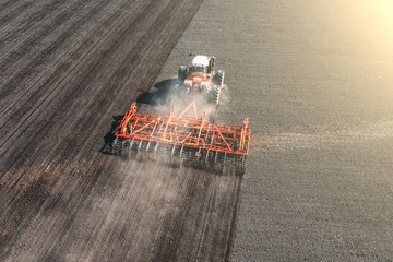 Top view of agricultural industrial tractor plows soil field for sowing , aerial view. Land cultivation