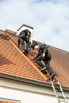 Two chimney sweeps climbing up house roof