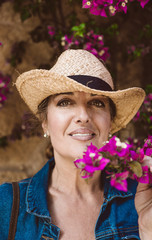 Woman wearing a hat looking at camera while standing near a wall with pink flowers shrubs