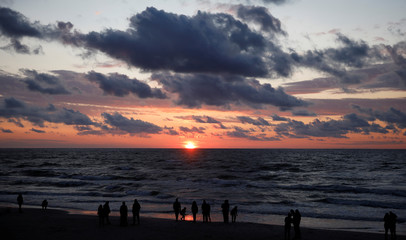 People stand at the beach during sunset at the Polish Baltic Sea coast near Choczewo