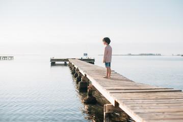 Boy standing on wooden pier