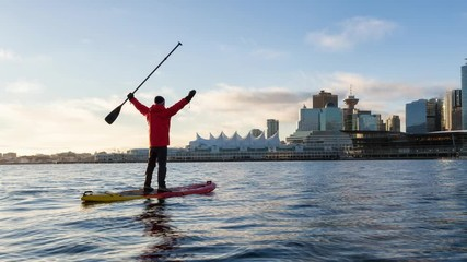 Wall Mural - Adventurous man is paddle boarding near Downtown City during a vibrant winter sunrise. Taken in Coal Harbour, Vancouver, British Columbia, Canada. Still Image Continuous Animation