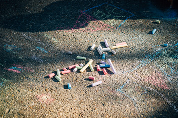 From above red blue green purple chalk and children drawings on asphalt in sunny day