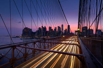 Brooklyn Bridge with light trails and view on Lower Manhattan just after Sunset. Evening in New York City, NY, USA