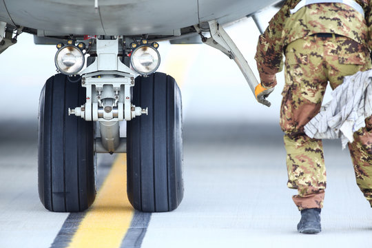 An army mechanic is inspecting the landing gear of a military cargo plane.