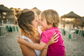Smiling mother and son rubbing noses while standing on beach