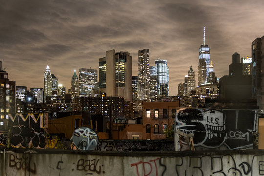 Manhattan bridge view over Chinatown at night, lower Manhattan in the background. New York City, United States of America.