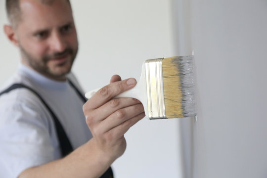 Man painting with a paintbrush over a grey wall